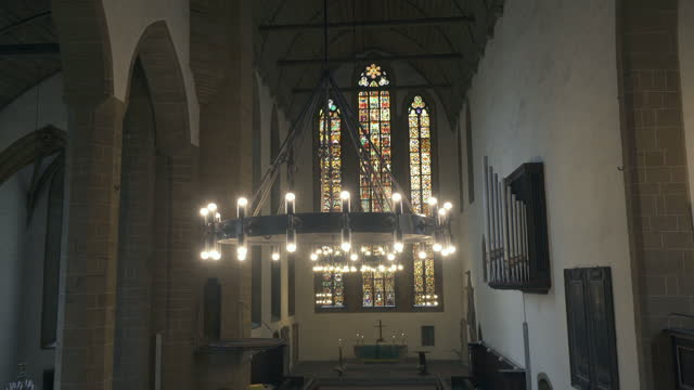 panning a lit chandelier hanging in an old german church with soaring stained glass windows, arches, vaulted ceiling, and stone carvings - erfurt, germany - apse stock videos & royalty-free footage