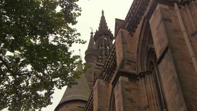 panning a lush green tree and the outside wall and towers of glasgow university, with red sandstone bricks and arched church windows - temple building stock videos & royalty-free footage