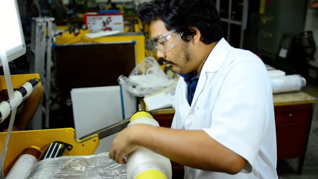 panorering: en chefsingenjör rulla blåst plastfilm på blåst film extruder