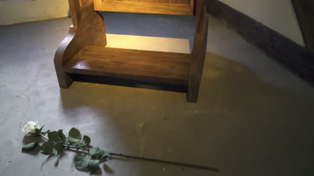 panning a single white rose lying on the floor next to a wooden prayer kneeler in an old german monastery with dramatic lighting, and a rustic cracked concrete floor - erfurt, germany - single rose stock videos & royalty-free footage