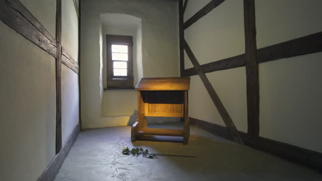 panning a small prayer room in an old german monastery with a single wooden prayer kneeler, a white rose, dramatic lighting, and old timber framed walls - erfurt, germany - single rose stock videos & royalty-free footage