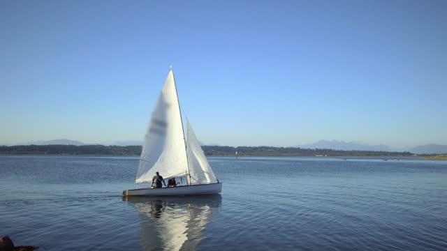 panning a small sailboat as it sails along a lakeside shore with bright blue sky and distant mountains - british columbia, canada - ship stock videos & royalty-free footage