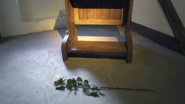 panning a wooden prayer kneeler in the small room in an old german monastery with a single white rose lying on the floor, dramatic lighting, and old timber framed walls - erfurt, germany - single rose stock videos & royalty-free footage