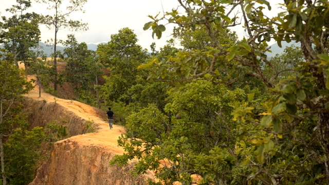 panning: a young adult running into a narrow peak of sand mountain - mae hong son province stock videos and b-roll footage