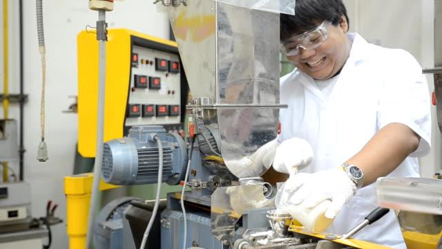 panorering: en ung ingenjör Häll plastpärlor i extruder