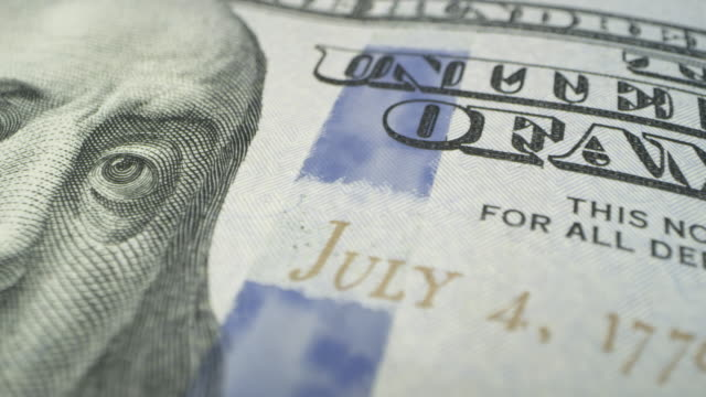 Panning across 100 dollar bill in maco view