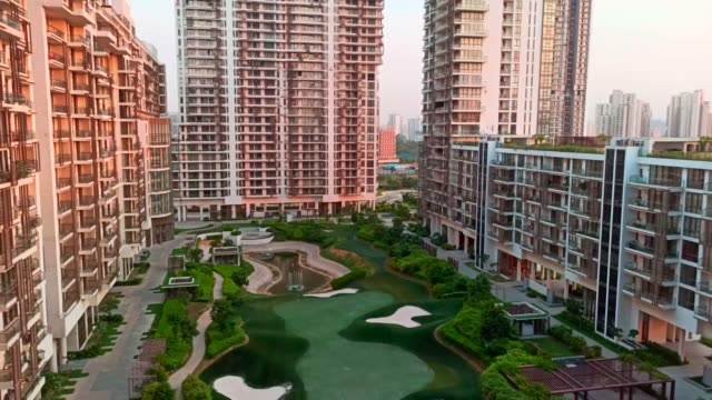 panning across a multistoried apartment complex wide view of the urban sprawl in a modern indian city at sunset dusk - organised group stock videos & royalty-free footage