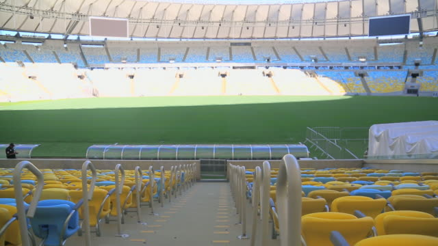 vídeos de stock e filmes b-roll de panning across aisle in empty maracana stadium stands - football