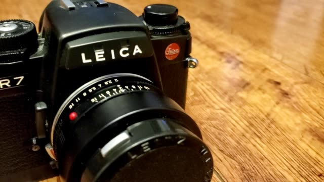 panning across leica r7 analog film camera on light wooden surface, with 50mm prime lens attached, san ramon, california, november 27, 2019. - wooden floor stock videos & royalty-free footage