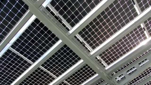 panning across low angle view of solar panels on a solar carport or parking lot cover, san ramon, california, january 30, 2020. - parken stock-videos und b-roll-filmmaterial