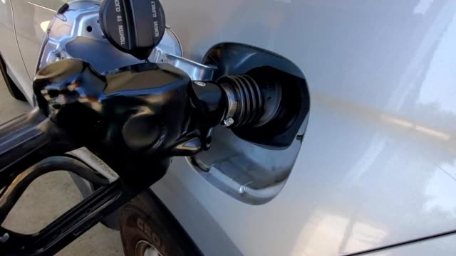 panning across nozzle of gas pump inserted into the gas tank of an automobile at a gas station in san ramon california september 11 2019 - fuel pump stock videos & royalty-free footage
