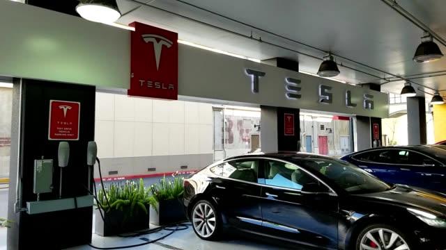 vidéos et rushes de panning across tesla motors automobiles parked in a test drive area in the silicon valley, san jose, california, march 15, 2019. - essai de voiture