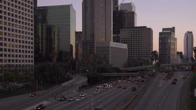 panning across the downtown los angeles skyline and 110 freeway at sunset - 金融関係施設点の映像素材/bロール