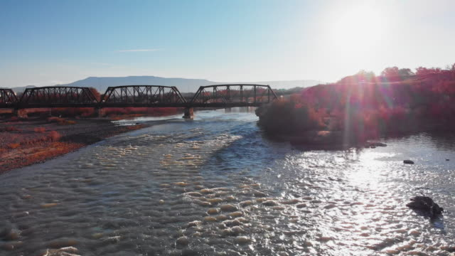 panning aerial drone shot of the confluence (meeting) of the colorado and gunnison rivers in the middle of the town of grand junction, colorado in autumn with mt. garfield and the grand mesa in the background - gunnison stock videos and b-roll footage
