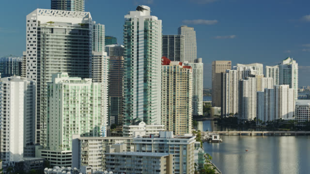 panning aerial shot of condos, hotels and office buildings in downtown miami and brickell key - biscayne bay stock videos & royalty-free footage