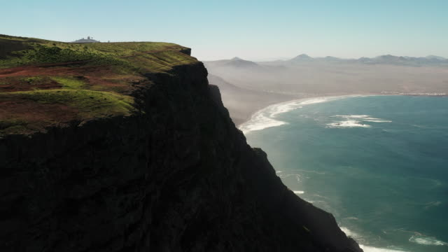 panning aerial shot showing a cliff face on the lanzarote coastline, spain - atheism stock videos & royalty-free footage
