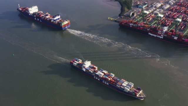 panning aerial shot showing container ships leaving a loading dock, netherlands - harbour stock videos & royalty-free footage