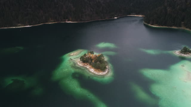 vídeos de stock, filmes e b-roll de panning aerial shot showing lake eibsee, germany - montanha zugspitze