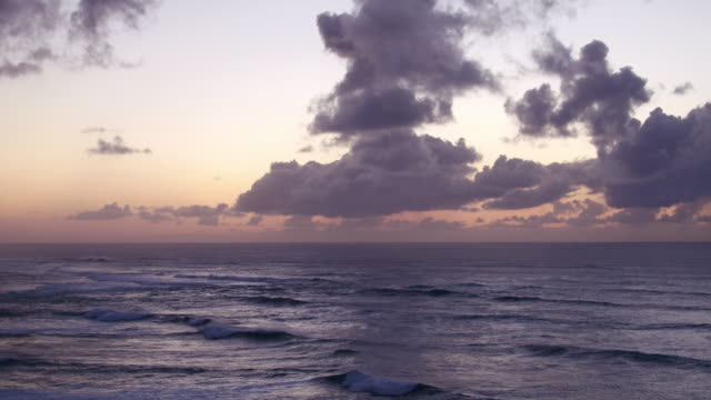 panning aerial shot showing waves crashing on shore at dusk - turtle bay hawaii stock videos and b-roll footage
