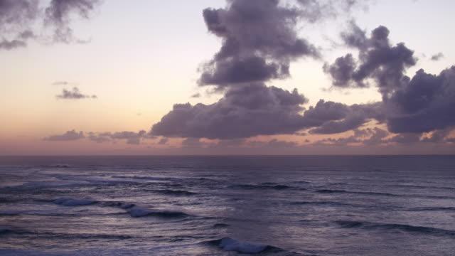 panning aerial shot showing waves crashing on shore at dusk - turtle bay hawaii video stock e b–roll