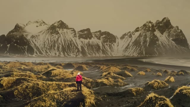 panning aerial view of mature woman exploring stokksnes beach with vestrahorn mountains in the background - mature women stock videos & royalty-free footage