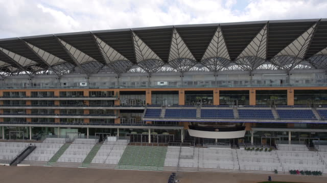 panning aerial view of the new grandstand at ascot racecourse - captured by a licensed uav operator with pfaw - イギリス アスコット競馬場点の映像素材/bロール