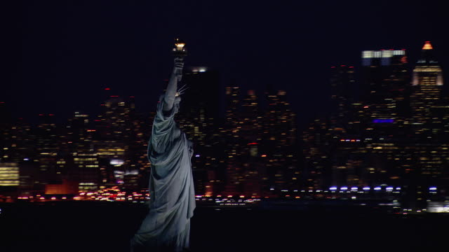 vídeos de stock, filmes e b-roll de panning aerial view of the statue of liberty and manhattan skyscrapers illuminated at night. - estátua
