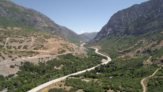 panning aerial view of winding roads leading up canyon - provo stock videos & royalty-free footage