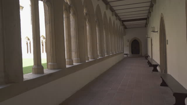 panning an arcade covered walkway in an old monastery with soaring arched columns, a green courtyard, and a view of other buildings within the complex seen beyond the arches - erfurt, germany - other点の映像素材/bロール
