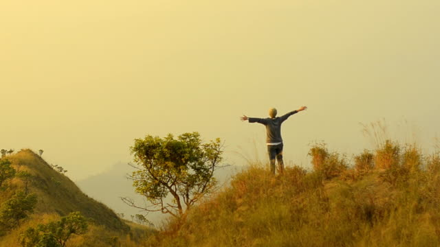 panning: arm-raised young adult happy in natural mountain