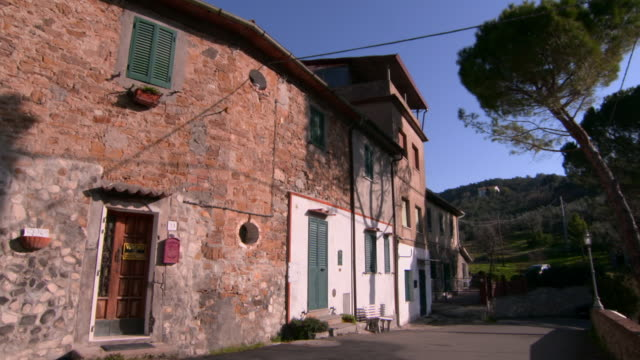 vídeos de stock e filmes b-roll de panning around old stone building with newer extensions in lucca, tuscany - cena não urbana