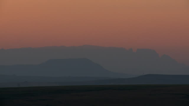 Panning WS at dusk of layers of blue lit mountains in background, KwaZulu-Natal, South Africa