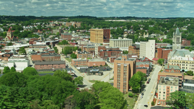 panning backwards drone shot over rooftops and church spires of uniontown, pennsylvania - street name sign stock videos & royalty-free footage
