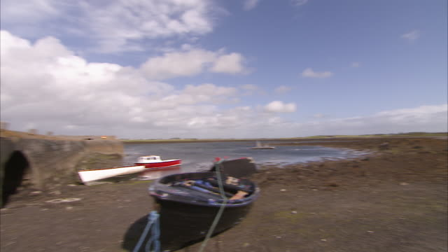 panning beached row boat with beautiful landscape - low tide stock videos & royalty-free footage