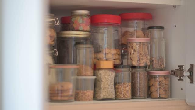 vídeos y material grabado en eventos de stock de armario panorámico lleno de botella de comida seca, comida conservada, galletas, nueces, bocadillo, dulces, alimentos crudos, harina, cereales - bandeja