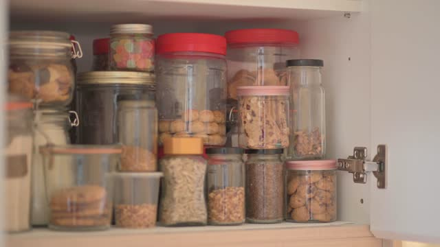 vidéos et rushes de placard d'armoire de panoramique plein de bouteille de nourriture séchée, nourriture préservée, biscuits, écrous, casse-croûte, sucrerie, nourriture crue, farine, céréales - placard