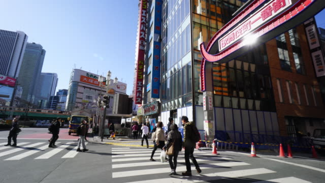 panning camera captures kabukicho and intersection at yasukuni-doori in shinjuku tokyo. shinjuku subcenter skyscrapers can be seen in behind jr line. - 日本語の文字点の映像素材/bロール