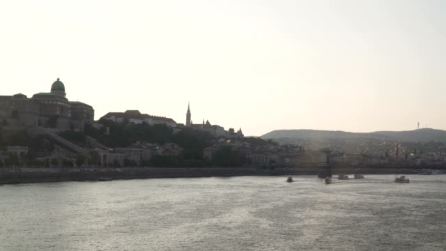 panning city view around danube river that consisted of castle hill from elisabeth bridge on sunset in budapest, hungary - royal palace of buda stock videos & royalty-free footage