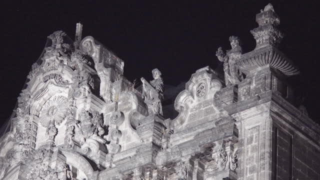 panning. close up. the frontal aspects of catedral metropolitana by night: skulls, statues, tezontle bricks, crosses. the many architectonic styles... - 映像技法点の映像素材/bロール