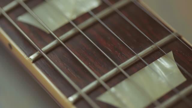 vídeos de stock, filmes e b-roll de garimpando próximo vídeo do pescoço de guitarra elétrica - rock moderno