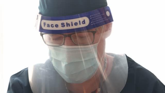 穿著面罩和面罩的醫護人員向下看的平移特寫 - 僅一成熟男士 個影片檔及 b 捲影像