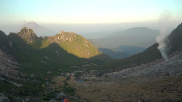 vídeos y material grabado en eventos de stock de panning: multitud de viajeros acampando en el cráter de la montaña sibayak por la mañana - monte sinabung