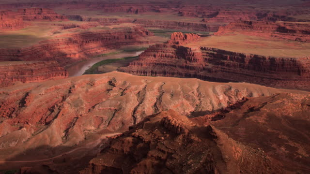 A panning day to night time lapse of Dead Horse Point State Park (outside of Moab, Utah) featuring the Colorado River, with heavy cloud cover moving across the sky, resulting in deep shadows rolling across the landscape in multiple directions.