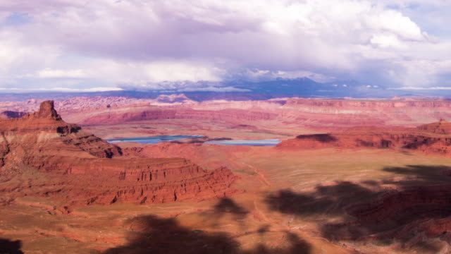 A panning daytime time lapse of Dead Horse Point State Park (outside of Moab, Utah) with heavy cloud cover moving across the sky, resulting in deep shadows rolling across the landscape in multiple directions.