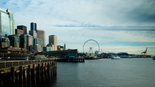 a panning daytime time lapse of elliott bay from the seattle waterfront with low hanging clouds overhead, featuring views of the seattle skyline, the great wheel, harbor island, west seattle, and the olympics. - elliott bay bildbanksvideor och videomaterial från bakom kulisserna
