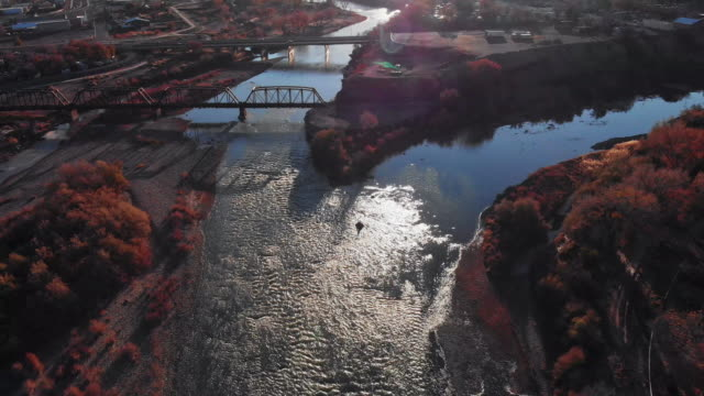 panning down aerial drone shot of the confluence (meeting) of the colorado and gunnison rivers in the middle of the town of grand junction, colorado in autumn with mt. garfield and the grand mesa in the background - river colorado stock videos & royalty-free footage