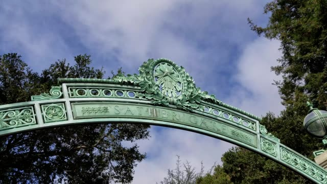 panning down from metalwork on the iconic sather gate entrance to uc berkeley in berkeley california to students and pedestrians approaching the gate... - città universitaria video stock e b–roll