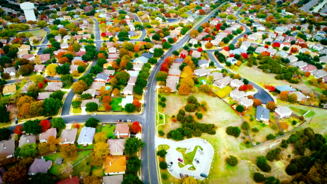 panning down to road fall foliage autumn suburb neighborhood housing development - modern rock stock videos & royalty-free footage