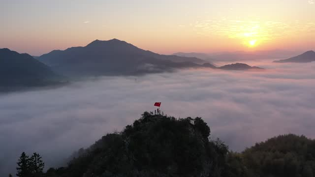 panning drone aerial video of a man waving a giant chinese flag on national day at sunrise at lu'an mountain in lu'an county, anhui province. - elevated view stock videos & royalty-free footage