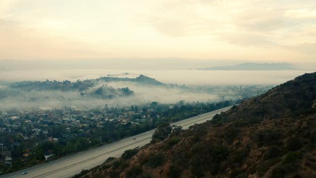 vidéos et rushes de tir de drone panoramique d'une vue brumeuse de los angeles - mauvais présage